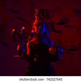 Halloween party and preparation concept. Kid in spooky witches costume holds jack o lantern and chandelier. Girl with confident face on bloody red background with decor. Little witch wearing black hat
