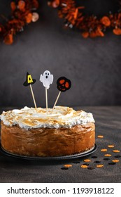 Halloween Party Pumpkin Cheesecake with Marshmallow Meringue Topping decorated with Halloween toppers. Dessert for Halloween and Thanksgiving. Space for text. Vertical. Selective focus.