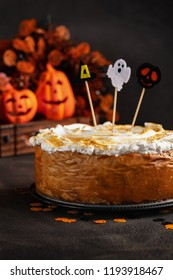 Halloween Party Pumpkin Cheesecake with Marshmallow Meringue Topping decorated with Halloween toppers. Dessert for Halloween and Thanksgiving Background. Space for text. Vertical. Selective focus.