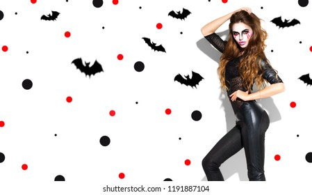 Halloween Party sexy girl makeup. Halloween Witch with bright vampire make-up and long hair, slim body. Beautiful young woman posing in witches costume. Isolated on white background with flying bats