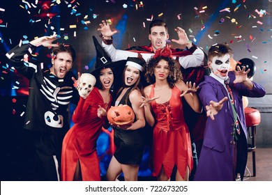 Halloween party. Six friends in costume cine villains posing with skull and pumpkin-lamp at a party for Halloween. Around them flies confetti. They are having fun and laughing