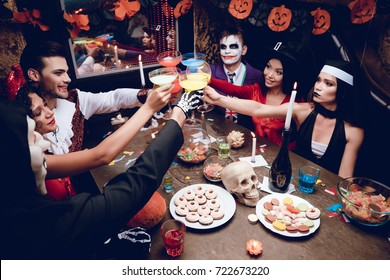 Halloween party. Six friends rest in a nightclub and sit at a table with colored cocktails. They have different sweets on the table. Everyone is having fun