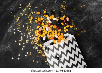 Halloween Party Trick of Treat Candy with candy flowing from  party favor bag on dark wood background  Flat lay, top view trendy holiday concept.