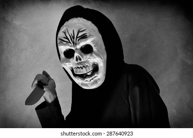Halloween party. Woman in black with a plastic human skull mask holding a knife