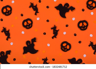 Halloween pattern background made of decorative ghost, witch, skeleton silhouette and pampkins confetti. Top view. Flat lay.