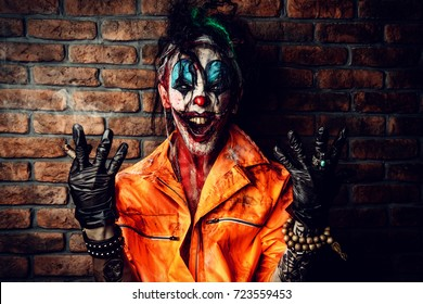 Halloween. Portrait of a bloodthirsty clown man over dark brick wall. Male zombie clown. Horror, thriller film.