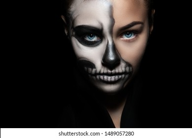 Halloween. Portrait of young beautiful girl with make-up skeleton on her face/ Closeup girl face with make-up skeleton