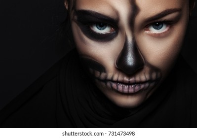 Halloween. Portrait of young beautiful girl with make-up skeleton on her face
