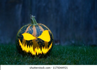 Halloween pumkin with spooky face on wooden background, space for text