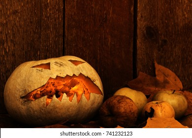 Halloween pumpkin and apples on autumn leaves next to a wooden background.