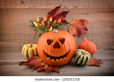 Halloween pumpkin and autumn flowers, on wooden background. Holiday card.