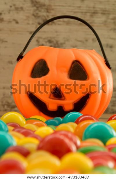 Halloween pumpkin basket full of candies on a wooden background