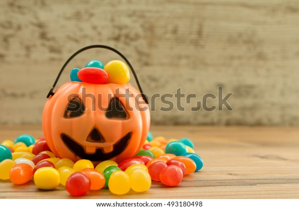 Halloween pumpkin basket full of candies on a wooden background