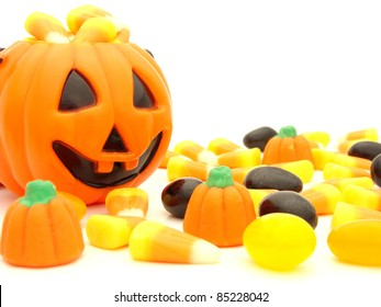 Halloween pumpkin behind a pile of scattered assorted candies against a white background