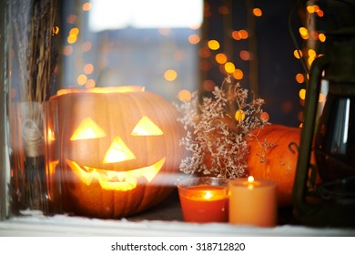 Halloween pumpkin and burning candles in window
