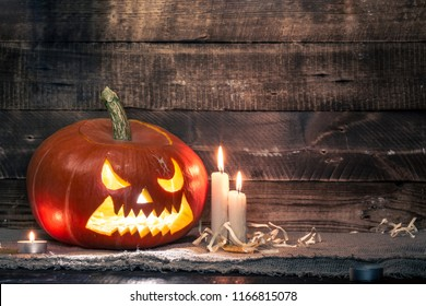 Halloween pumpkin and candles on a dark, wooden background. Halloween celebration. Copy space