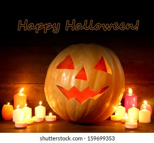 halloween pumpkin and candles, on wooden background