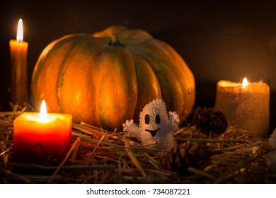 Halloween pumpkin and candles on wooden background. A  ghost on a leafs