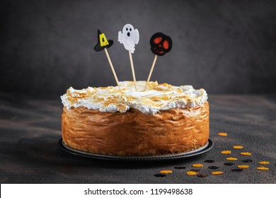 Halloween Pumpkin Cheesecake with Marshmallow Meringue Topping decorated with Halloween toppers. Dessert for Halloween and Thanksgiving. Space for text. Horizontal. Selective focus.