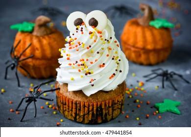 Halloween pumpkin cupcakes with funny meringue ghost, idea for Halloween party dessert selective focus