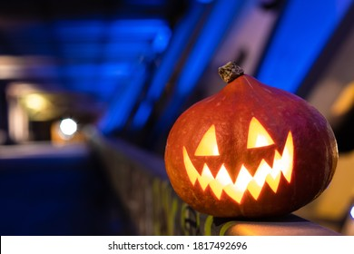 Halloween pumpkin in the dark on a blue industrial abstract background. Blurry colored lights. The decor of the night city in a festive Halloween theme. Copy space.