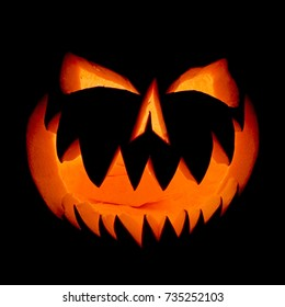 Halloween pumpkin face ghost glowing in the dark. Decoration illuminates and emerges from the darkness.