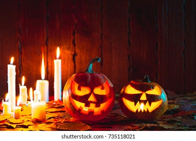 Halloween pumpkin with glowing face on a wooden background with candles.