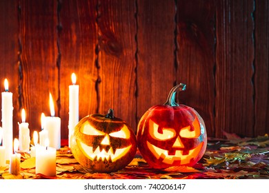Halloween pumpkin with glowing face on a wooden background with many flaming candles and autumn leaves. Idea for flyers, poster, placard, billboard