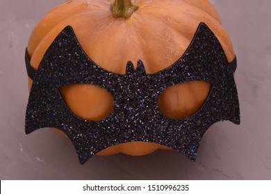 Halloween pumpkin head. Pumpkin head in a bat mask.
