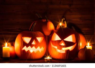 Halloween pumpkin head jack lantern and candles on wooden background