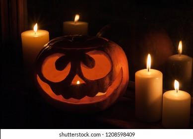 Halloween pumpkin head jack lantern with burning candles around staying at night near the window. Spooky Samhain.