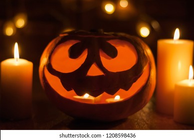 Halloween pumpkin head jack lantern with burning candles around staying at night near the window. Spooky Samhain.