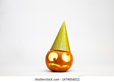 Halloween pumpkin head jack lantern with burning candles with festive hubcap isolated on white background