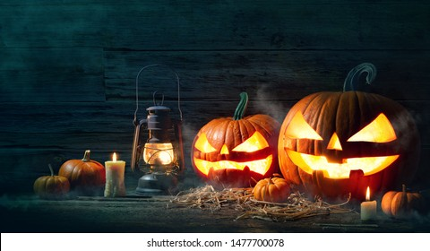 Halloween pumpkin head jack lantern with burning candles in scary deep night