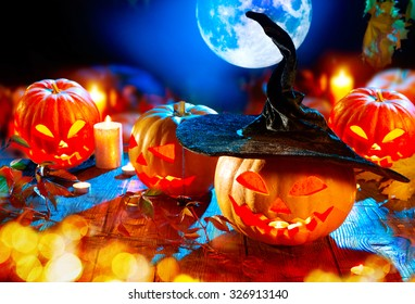 Halloween pumpkin head jack lantern with burning candles over black background. Halloween holidays art design, celebration