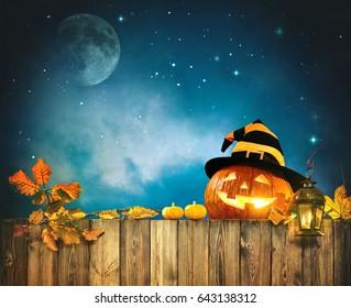 Halloween pumpkin head jack lantern on wooden fence