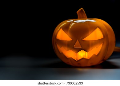 Halloween pumpkin head jack lantern on dark floor and background.Halloween party concept.