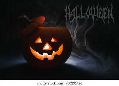 Halloween pumpkin head jack lantern on wooden background. Dark background with letters halloween and mysterous smoke.