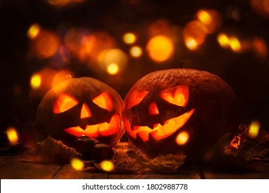 Halloween pumpkin head jack o lantern with burning fire background, wooden table  with light bokeh garland. Beautiful Holiday Autumn Composition