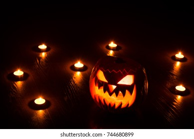 The Halloween pumpkin Jack lantern with an ugly look in its eye among burning candles