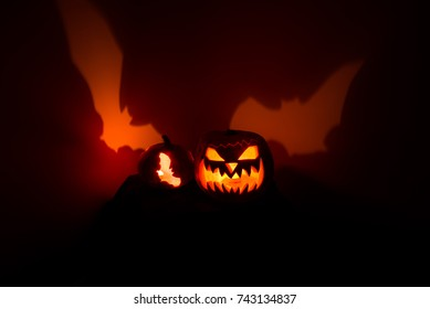 The Halloween pumpkin Jack lanterns with cutting throwing the shadows on the wall.