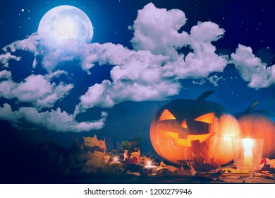 Halloween pumpkin Jack-o'-lantern on wooden table with candles in a spooky night over moon and clouds.