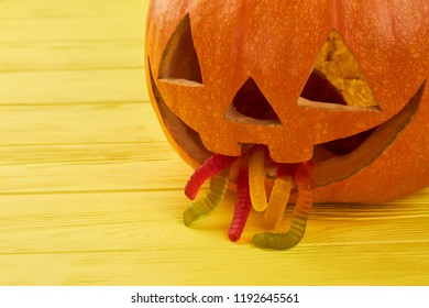 Halloween pumpkin with jelly worms in mouth. Puking pumpkin on yellow wooden background.