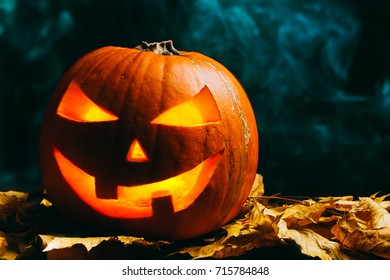 Halloween pumpkin lantern with dry leaves on a smoky dark background