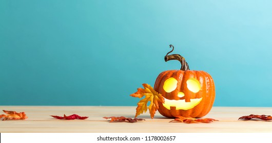 Halloween pumpkin with leaves on a blue background