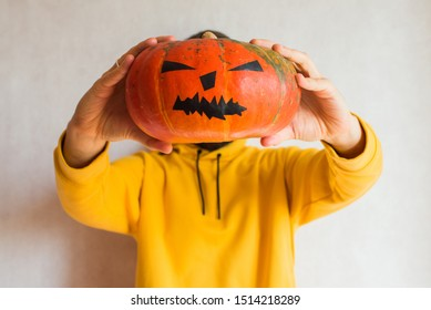 Halloween pumpkin. Man holding in hand a scary face pumpkin. Happy Halloween party holiday. Celebrate annual in October 31. Autumn season. Fall color, orange and yellow. Trick or treat. Pumpkin Day