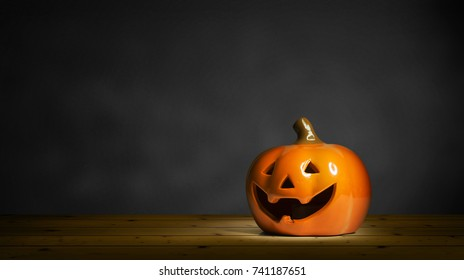 Halloween Pumpkin miniature decoration on plank wood table and dark background.