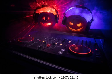Halloween pumpkin on a dj table with headphones on dark background with copy space. Happy Halloween festival decorations and music concept. Empty space. Selective focus