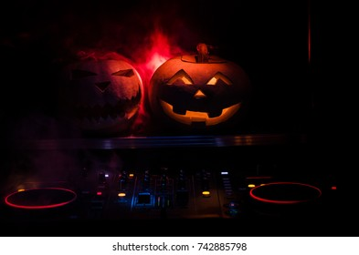 Halloween Pumpkin On A Dj Table With Headphones On Dark Background With  Copy Space. Happy