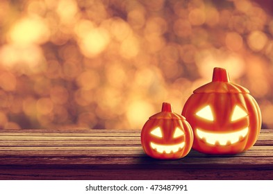 Halloween pumpkin on table wood with light orange bokeh background, halloween background concept, copy space.